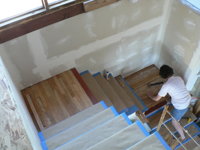 Gail Fits Pieces Of Hardwood Flooring Onto The Lower Stair Landing
